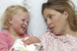 (BOULDER, Colo., March 3, 2005) Lili,4, holds Poppy, her new sister, while mom, Deli chats with...