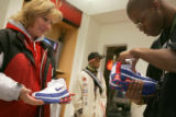 02/17/2005 Denver, Colorado-Niketown employee Mario Avent checks the size of a pair of Nike Shox...
