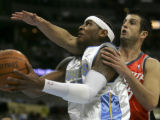 (DENVER, Colo., March 16, 2005)  Carmelo Anthony drives past Jason Kapono in the first quarter of...