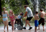 {DENVER, COLO., JUNE 8, 2004}--  Steve Rider and his son, Gordon Rider, 11, (center) cool off from...