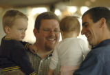 (DENVER, CO., March 17, 2005) Cameron Thomas holding his 21 month old son, Brandon, left, and Ned...