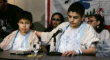 Lance Crow, 15, left, and Cody Thunder, 15, right (at mic), prepare to address reporters Thursday...