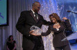 (Denver, Colo., February 18, 2005) Alonzo Mourning, left, and Patti LaBelle, right, dance on stage...