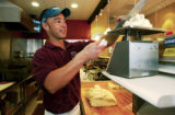 (Ft. Collins, Colo., Mar. 28, 2005) CU Regent Tom Lucero (cq), cuts pizza dough to right weight as...
