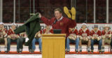 (Denver, Colo., April 13, 2004) Colorado Governor Bill Owens holds up a jacket and a pair of boots...