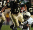 (LAKEWOOD, CO., OCTOBER 22, 2004)  Colorado State' #18, Jimmy Green, left, drags Wyoming's #1,...