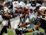 (OAKLAND, CA., OCTOBER 17, 2004)  Denver Broncos' #34, Reuben Droughns, left, breaks through...