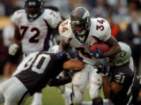 (OAKLAND, CA., OCTOBER 17, 2004)  Denver Broncos' #34, Reuben Droughns, center, splits  Oakland...