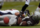 (OAKLAND, CA., OCTOBER 17, 2004)  Oakland Raiders' #84, Jerry Porter, right, lays sprawled out on...