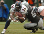 (OAKLAND, CA., OCTOBER 17, 2004)  Denver Broncos' #26, Tatum Bell, left, dives for additonal...