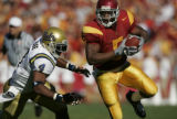 105088.SP.1203.trojans37.GMF - USC's Reggie Bush eyes an opening with UCLA Bruin Jarrad Page on...