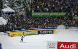 American skiier Daron Rahlves raises his arms in celebration after crossing the finish line at the...