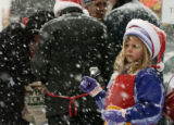 Bridget Anderson, 7 years old from Littleton, rings the bell for the Salvation Army in the cold...