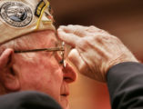 Pearl Harbor survivor David Wilson, cq, 85, salutes as taps is played during a ceremony honoring...
