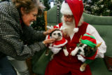 Pam Blackman (cq), left, of Thornton readies her dog, Tinkerbull, for a photo with Santa at...