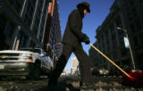 Brad Barkey (cq), doorman at the Hotel Monaco, shovels snow from the street in front of the Hotel...
