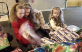 Sisters (l-r) Lynette, 7, Kayla, 12, and Nicole Golden, 4, open presents in the front lobby of The...
