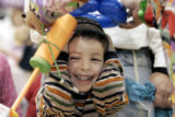 Adiv Karr, 4, (cq from dad)  from Denver is all smiles as he gets a balloon hat from Skiddles the...