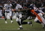 Denver Broncos Courtney Brown and Ian Gold stop Baltimore Ravens Chester Taylor on a fourth and...