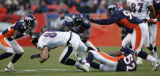 The Denver Broncos Defense swarms Baltimore Ravens TE Todd Heap in the third quarter as the...
