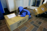 Gus Frank, 4 of Denver, rests on a Christmas package for his grandparents in Maryland, while his...
