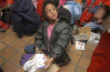 Tessa Gartrell (cq), age 7, looks up at friends after opening a box containing a pair of new...