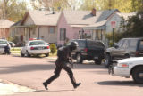 (DENVER, Colo., April 20, 2004) An armed and protected SWAT member quickly crosses the street. The...