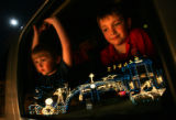 Andrew Kuzik, 4, left and his brother Collin Kuzik, 8, right peer out of the family Suburban as...