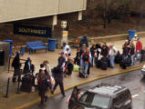 Southwest Airlines passengers wait in line as they arrive at Philadelphia International Airport...