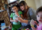 Jenny Woodson, cq, reads Sesame Street books with her daughters Ivy Medina, cq, 4, left, and Chloe...