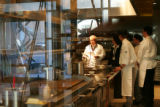 Guests can watch the chefs in action through the large window looking into the kitchen of...