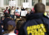 (Denver, Colo., April 19, 2004) A group of protestors hold sign and shout at police officers at a...