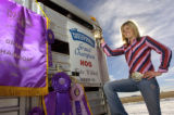 Kylee Winter, 18, of Hudson poses with a collection of her championship banners and belt buckles...
