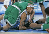 Denver Nuggets forward Kenyon Martin, middle, fights for the ball with Boston Celtic guard Delonte...