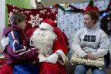(DENVER., Colo., Dec. 19, 2005) Andrew Bott, 12, (left_cq) sits on Santa's laps, Monday Dec. 19,...