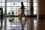 Amy Davis, cq, laundry manager at the Hyatt Regency Hotel in downtown Denver, sweeps the lobby in...