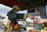 Hot dog vendor Valentina Petty gives change to a customer near a Wolfgang Puck Express eatery in...