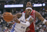 Denver Nuggets forward Carmelo Anthony, middle, drives to the basket being guarded by Houston...
