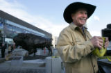 Artist T.D. Kelsey finishes installing his 3,000 pound bronze North American bison on the...