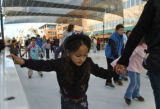 Nicole Justino, 6 years old, goes around the ice skating rink with her mom Christine Justino (cq),...