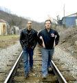 Shown: Cody Perkins (left) and Chris Johnson (right) walk the train tracks through their hometown...