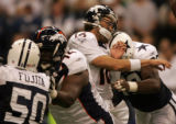 RG448 Denver Broncos' quarterback, #16, Jake Plummer, center, is drilled in the head by Dallas...