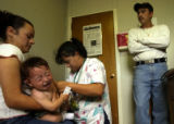 Denver, Colo., April 14, 2004- 9-month-old Essai Marin gets a booster shot by medical assistant,...