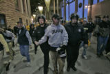Boulder county sheriff's department officers escort an unruly fan from Folsom Field after refusing...