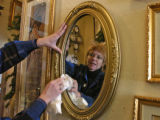 Teresa Warren (cq) cleans a mirror in her store, Off Her Rocker, 4 east First Street in Nederland,...
