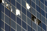 An unidentified worker removes glass from a broken window in the Plaza Tower building at 18th St....