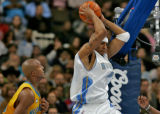 Nuggets forward Kenyon Martin, right, grabs a rebound over  New Orleans/Oklahoma City Hornet...