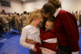 CW3 Sam Flaten, a Medivac (short for Medical Evacuation), pilot, hugs his daughter, Bailey Flaten,...