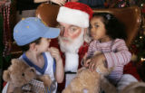 (L-R) Adrian Garcia,5 listens as  Kaila Stafford, 4, whispers her wishes to Santa at the Denver...