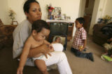 (LT. to RT.) Seven-month-old Jonathan Anguiano (CQ), sits on mother Carmen Simental (CQ), 26, lap...